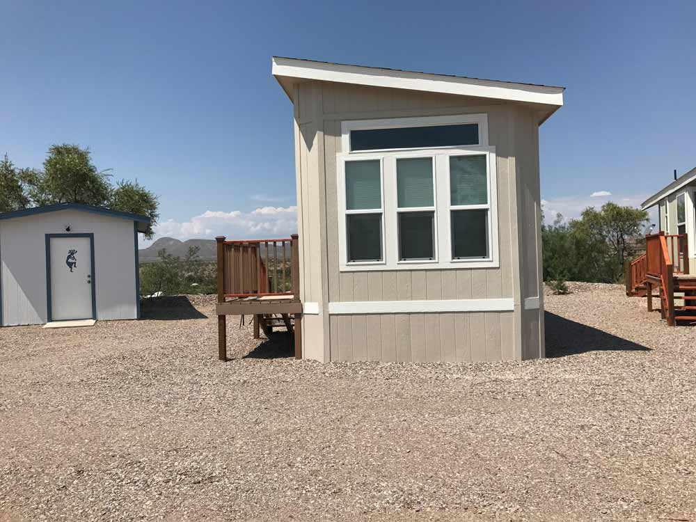 tan park model with storage shed at cedar cove rv park